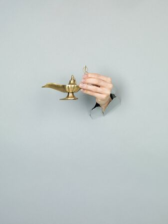 lady with the lamp: close-up of female hand holding a magic lamp through a torn grey paper