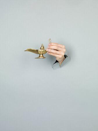 alladdin: close-up of female hand holding a magic lamp through a torn grey paper
