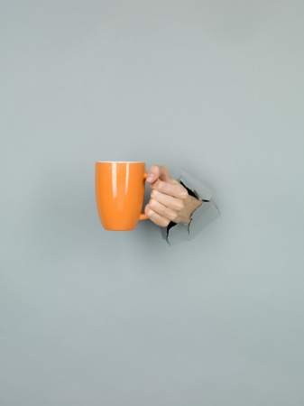 close-up of female hand holding an orange cup through a torn grey paper photo