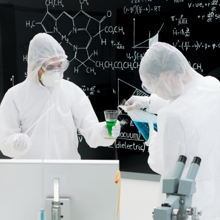 chlorophyll: close-up of two people chemically testing substances in a laboratory with transparent tools and colorful liquids with a blackboard on the background
