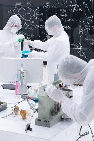 magical equipment: close-up of three people in a laboratory testing and applying chemical procedures using transparent tools and  colorful liquids on a lab table with a blackboard with formulas on the background