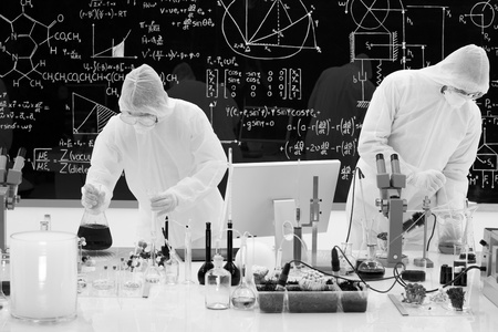 general-view  of two people manipulating laboratory tools, analysing and aplying chemical techniques  using transparent laboratory tools and black liquids on a lab table with a blackboard on the background
