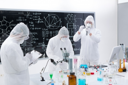 manipulating: general-view of three scientists in a chemistry lab  manipulating lab tools, testing and using chemical techniques around a lab table with a blackboard on the background Stock Photo