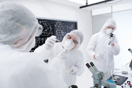 psilocybin: close-up of three researchers analysing and evaluating chemical reactions in a chemistry lab using lab tools and a blackboard on the background