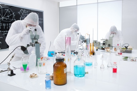 worktable: general-view of  three people observing and analysig chemical reactions in a lab  using colorful substances and lab tools  on a lab worktable with a blackboard on the background
