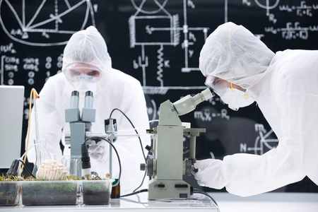 worktable: close-up  of two scientists manipulating microscopes in a chemistry lab on a worktable with a blackboard on the background