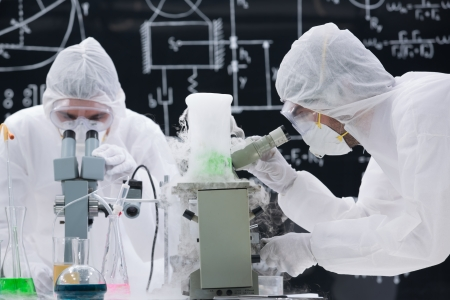 pharmacology: close-up   of two scientists analyzing under microscope in a chemistry lab with a blackboard on the background
