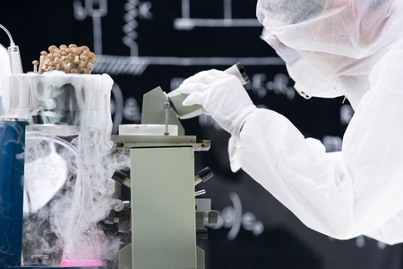 psilocybin: close-up of man analyzing under microscope in a chemistry lab around lab tools with mushrooms in gas and a blackboard on the background Stock Photo