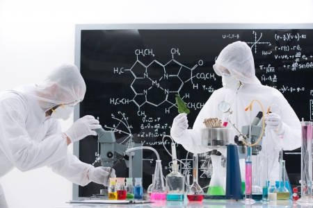 analytical: side-view of two people manipulating lab tools and colorful liquids on a lab table with a blackboard on the background Stock Photo