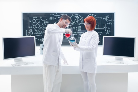 general view of two people manipulating laboratory flasks with colorful liquids in a chemistry lab with a worktable and a blackboard on the background