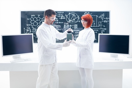 worktable: general-view of a man and a woman holding in hands a grey container in a chemistry lab with a worktable and a blackboard on the background