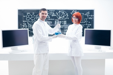 worktable: general view of a man and a woman in a chemistry lab holding in their hands a flask containing blue liquid and a worktable and a blackboard on the background