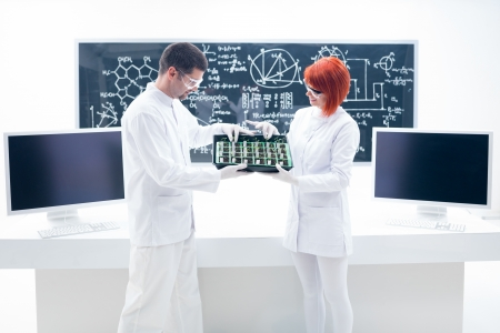 globalwarming: general view of two people analyzing seedlings on a chemistry lab with a worktable and a blackboard on the background Stock Photo