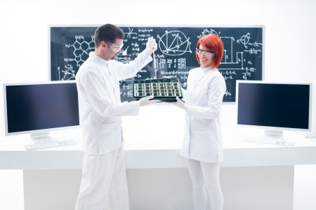 manipulating: general view of one woman holding seedling in hands and a man manipulating lab tools in a chemistry lab with a blackboard on the background