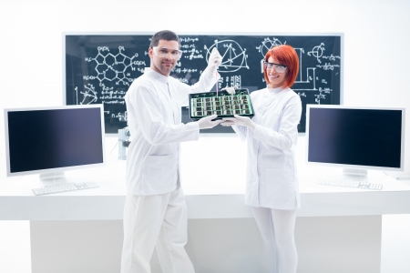 manipulating: general view of two people manipulating seedlings in a chemistry lab with a worktable and a blackboard on the background Stock Photo