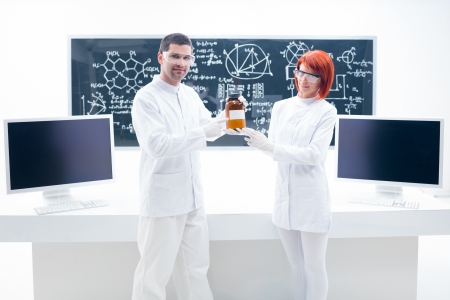general- view of a man and a woman holding in hands an orange  container in a chemistry lab with a worktable and a blackboard on the background