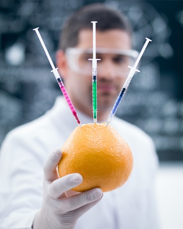 macro of a handheld injected  grapefruit by a man  in a chemistry lab