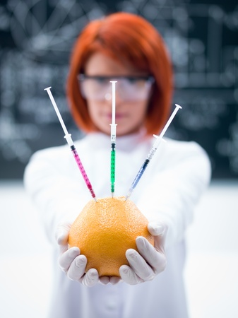 macro of a handheld injected  grapefruit by a woman  in a chemistry lab 版權商用圖片
