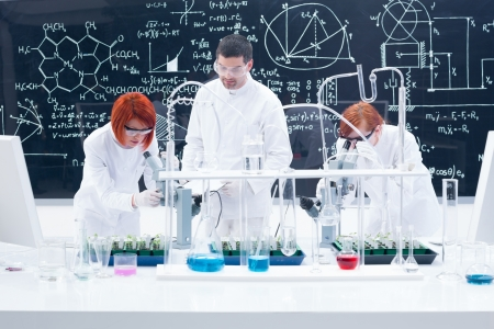 manipulating: general-view of one man in a chemistry lab supervising two women manipulating lab tools with colorful liquids and seedlings on a lab table with a blackboard on the background