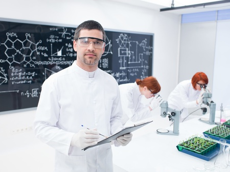 close-up of scientist in a chemistry lab with two women in the background  chemically analysing  under microscope and a blackboard on the background