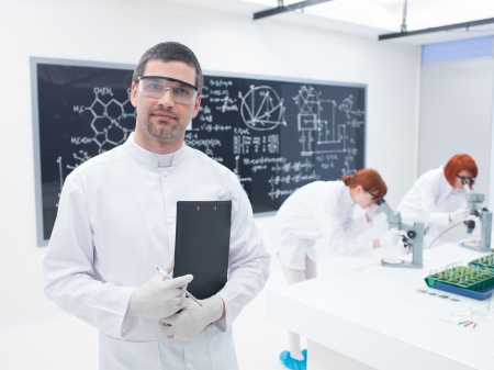 chemically: close-up of scientist in a chemistry lab smiling  with two women in the background  chemically analysing  under microscope and a blackboard on the background