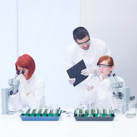 globalwarming: close-up  of a teacher in a chemistry lab supervising the activity on two students analyzing plants on a lab table and  observing reactions under microscope