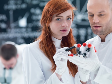 citric: close-up of a student in a chemistry lab analyzing  a citric acid molecular model holded by her teacher Stock Photo