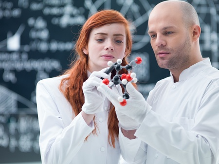 drug discovery: general-view  of a student in a chemistry lab analyzing  a citric acid molecular model holded by her teacher with a blackboard on  the background