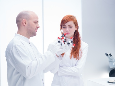 citric acid: sidel-view  of a student in a chemistry lab observing  a citric acid molecular model holded by her teacher Stock Photo
