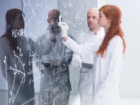 zijaanzicht van een student in een chemie lab schrijven op een schoolbord formules onder haar leraar toezicht