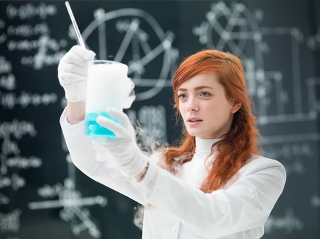 general-view  of a student analyzing blue liquids and gas in a chemistry lab with a blackboard on the background Stock Photo