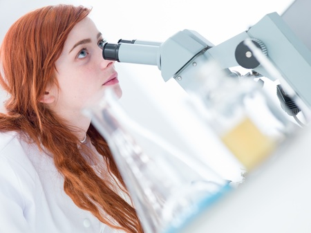 side-view of a student in a chemistry lab looking at her teacher while analyzing under microscope photo