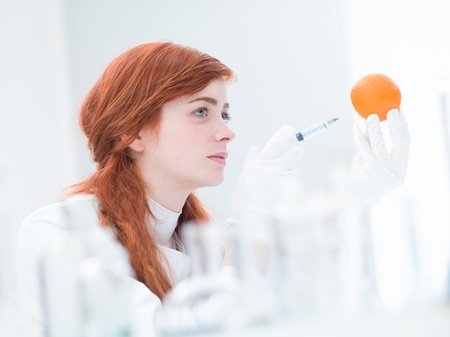 latex girl: close-up of woman in a laboratory injecting an orange