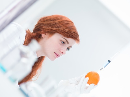 latex girl: close-up of woman in a laboratory analyzing an injected orange