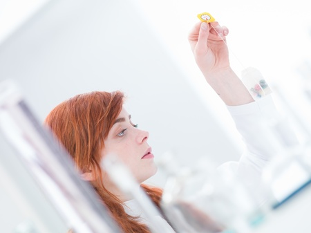 close-up of woman in a laboratory analyzing pills  in a tea bag photo