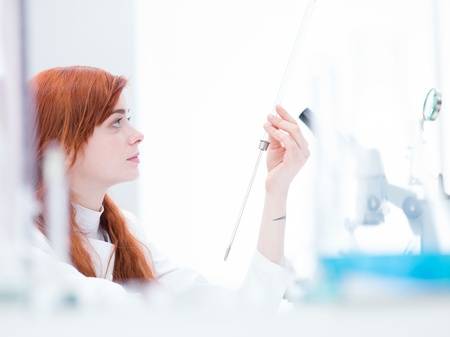side-view of one beautiful girl student holding in hand a  lab tool and analyzing it Stock Photo - 20635808