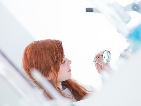 close-up of a girl student analyzing under a magnifier in a chemistry lab photo