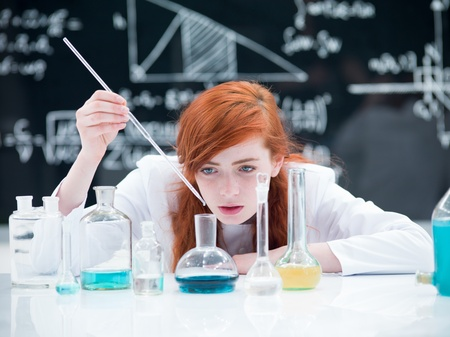 general-view of a student girl conducting a laboratory experiment on a lab table  with colorful liquids and lab tools with a blackboard on the background