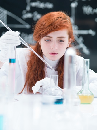 close-up of a student girl conducting a laboratory experiment on a lab table  with colorful liquids and lab tools with a blackboard on the background