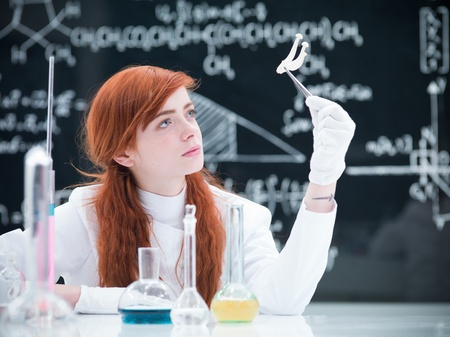 hallucinogen: close-up of a student in a chemistry lab analyzing a bunch of mushrooms around a lab table with colorful liquids and a blackboard on the background Stock Photo