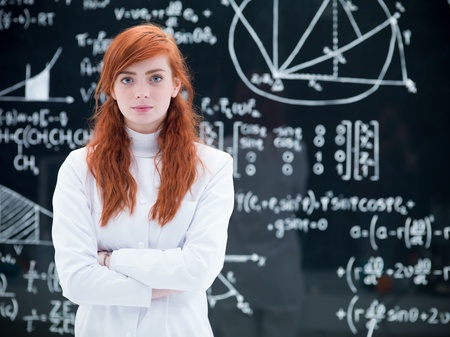 close-up of schoolgirl succesful looking  in the camera in a chemistry lab with a blackboard on the background photo