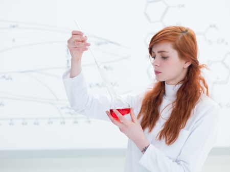 side-view of a beautiful girl student in a chemistry lab analyzing colorful substances and a transparent board on the background