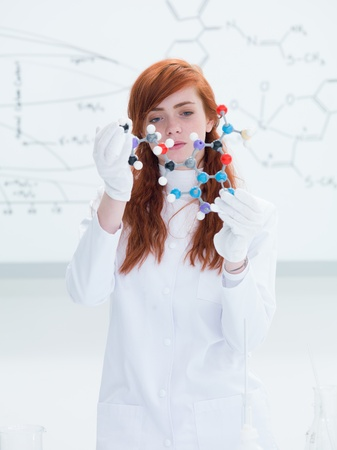 general-view of a student in a chemistry lab holding in hands and analyzing DMT molecular model and a white board on the background photo