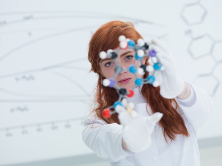 general-view  of a student in a chemistry lab looking in the camera and holding in hands and analyzing DMT molecular model and a white board on the background photo