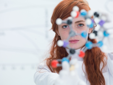 physic: macro of a student in a chemistry lab holding in hands and analyzing DMT molecular model