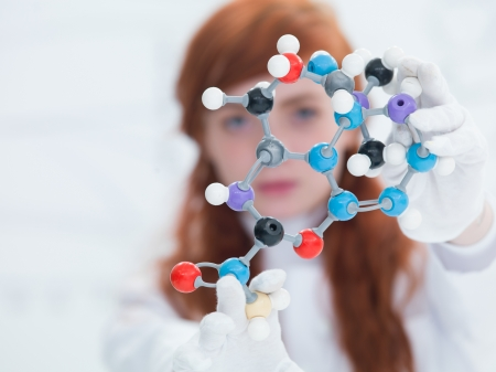 drug discovery: macro of a  DMT molecular model with a pretty girl face in the background