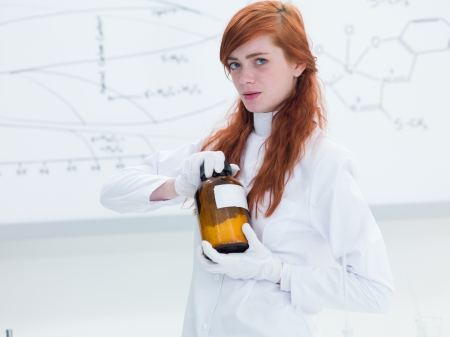 side-view of a student in a chemistry lab holding in hands and analyzing an orange recipient containing white powder and a transparent board on the background photo