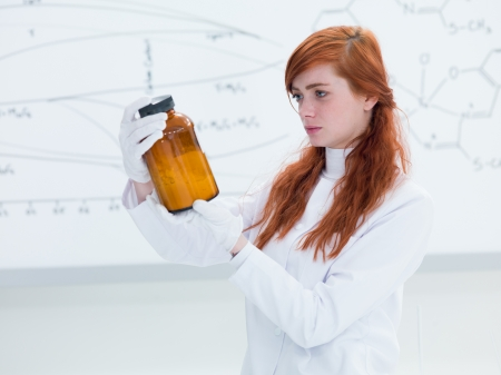 side-view of a student in a chemistry lab holding in hands and analyzing an orange recipient containing white powder and a transparent board on the background