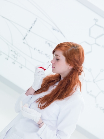 side-view of a pretty student in a chemistry lab smelling colorful substances and a white-board on the background 版權商用圖片