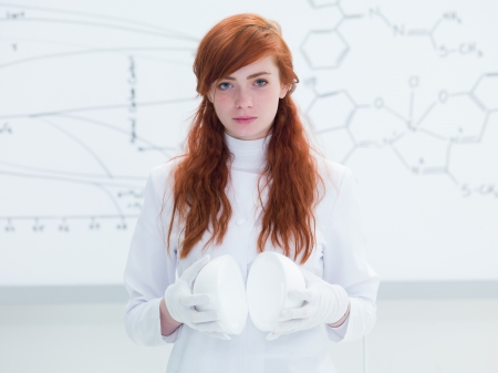 general-view of a pretty student portrait in a chemistry lab looking in the camera and holding in hands lab pots and a white-board on the background photo